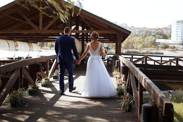 La mariée et le marié marchent main dans la main le long de la jetée en bois