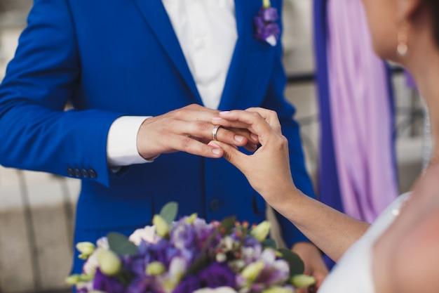 La mariée et le marié mettent au doigt une bague de mariage