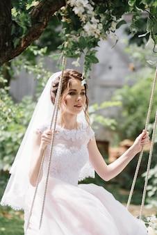 La mariée et le marié montent une balançoire dans le jardin. mariage dans la forêt.