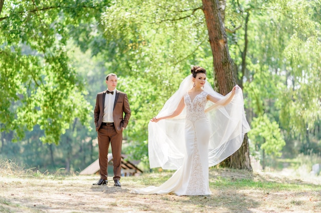 La mariée et le marié posant à l'extérieur devant la caméra. concentrez-vous sur la mariée.