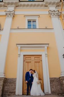 La mariée et le marié s'embrassent près d'un bel immeuble