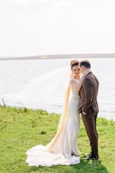 La mariée et le marié s'étreignent près de l'étang dans la nature. le vent lève un léger voile.