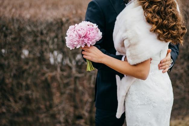 Mariée et le marié sans visage dans les vêtements de fête, embrasser et se tenir étroitement, femme en robe blanche