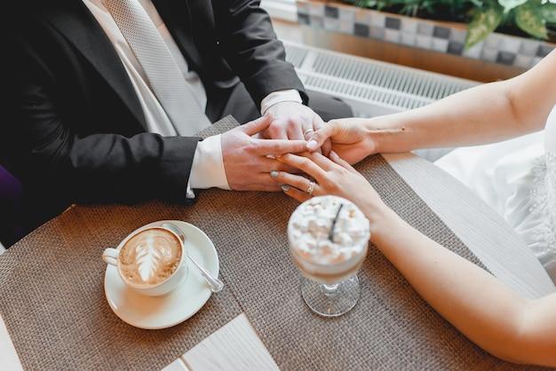 Mariée et le marié se tenant la main. un moment romantique. cappuccino et latte aux guimauves.