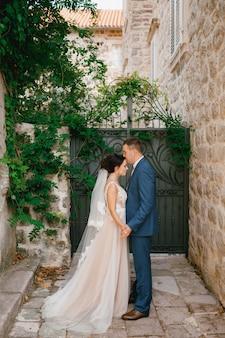 La mariée et le marié se tiennent la main dans une petite cour près de la porte forgée, le marié embrasse