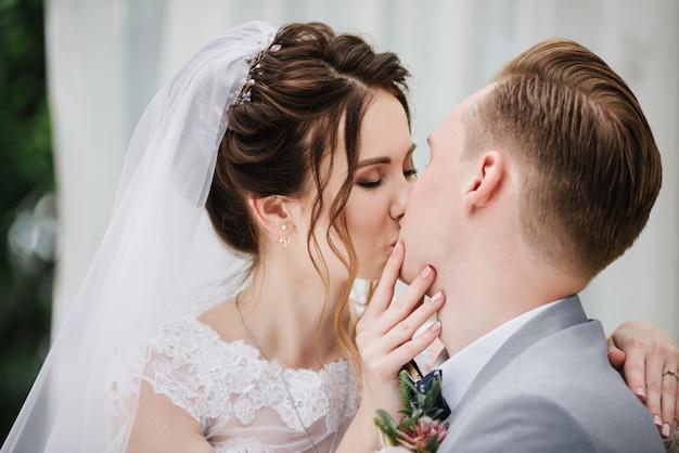 La mariée et le marié sont assis sur un beau canapé dans un kiosque dans le jardin et s'embrassent. un portrait rapproché. tente blanche. feuillage vert. la mariée dans une robe duveteuse rose, le marié dans un costume gris.