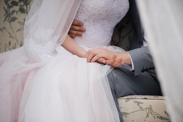 La mariée et le marié sont assis sur un beau canapé dans un kiosque dans le jardin et se tiennent par la main. tente blanche. feuillage vert. la mariée dans une robe duveteuse rose, le marié dans un costume gris.