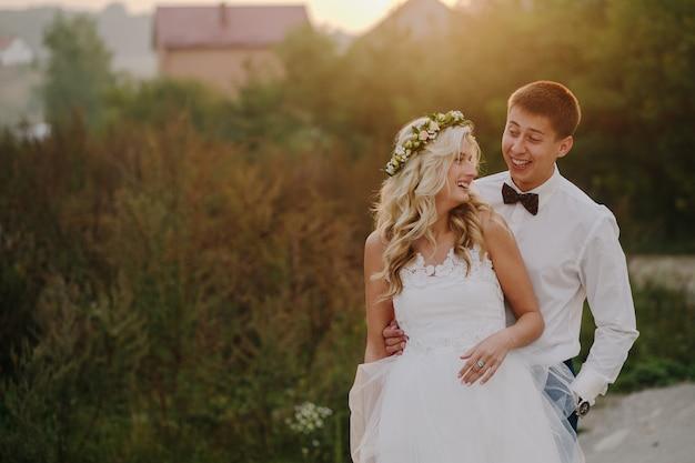 Mariée et le marié en souriant avec un fond défocalisé