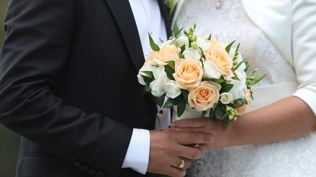 Mariée avec le marié tenant le bouquet de mariage à la cérémonie