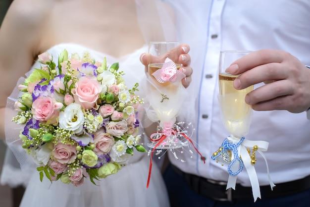 La mariée et le marié tenant des lunettes de mariage et un beau bouquet délicat en gros plan