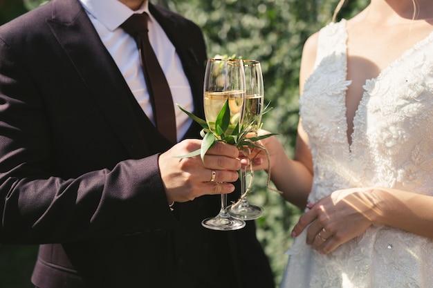 La mariée et le marié tiennent des verres en cristal remplis de champagne