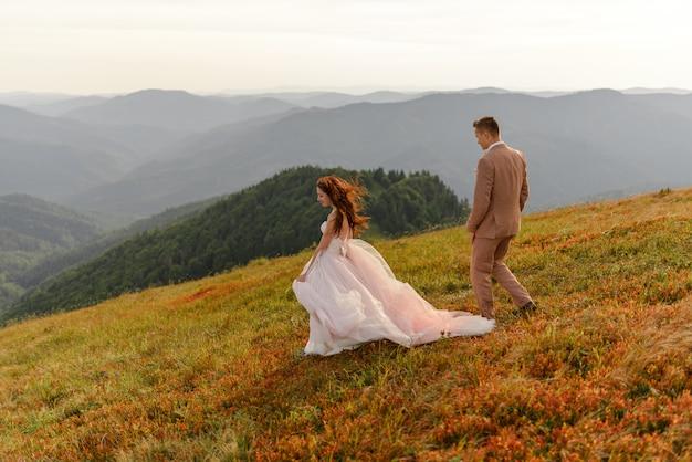 La mariée et le marié vont côte à côte. le coucher du soleil. photo de mariage sur fond de montagnes d'automne. un vent fort gonfle les cheveux et la robe.