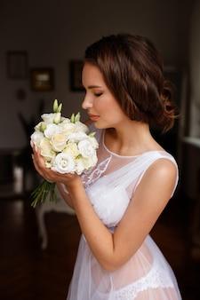 Mariée le matin avec un bouquet de fleurs