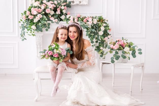 Mariée mère et fille en robes blanches avec des fleurs