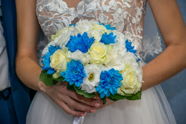Une mariée merveilleuse tient un bouquet de mariage dans ses mains pendant la cérémonie de mariage.