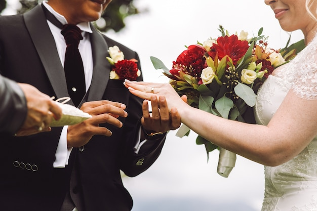 La mariée met l'alliance au doigt du marié