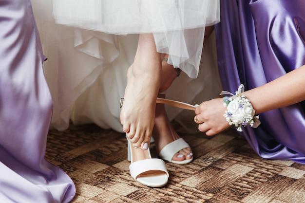 La mariée met des chaussures de mariage blanches