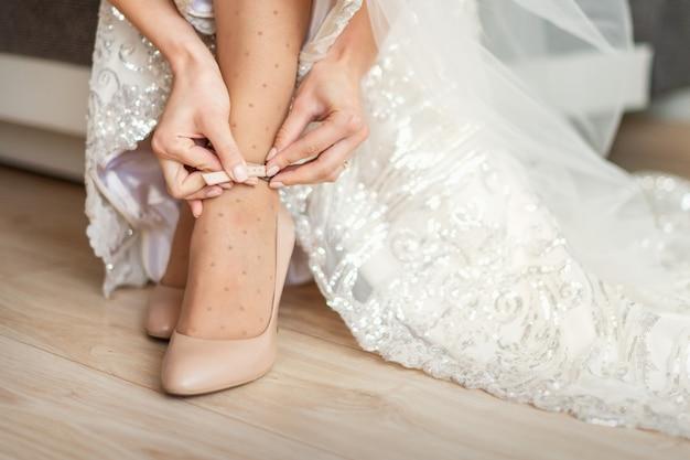 La mariée met des chaussures de mariage