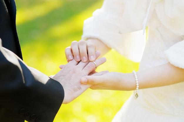 Mariée mettant une alliance au doigt du marié
