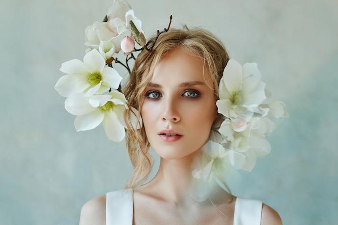 Mariée parfaite avec des bijoux, fille portrait en longue robe blanche. de beaux cheveux et une peau délicate et propre.