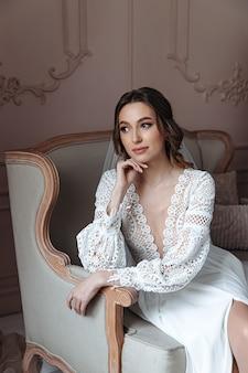 Mariée pensive posant dans un fauteuil dans une robe de mariée de style bohème.