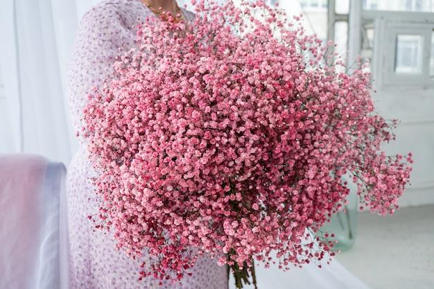 Mariée plus la taille tenant le bouquet de fleurs rose gipsofila