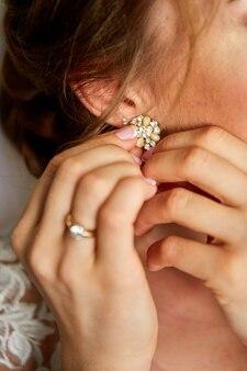 Mariée portant des boucles d'oreilles gros plan