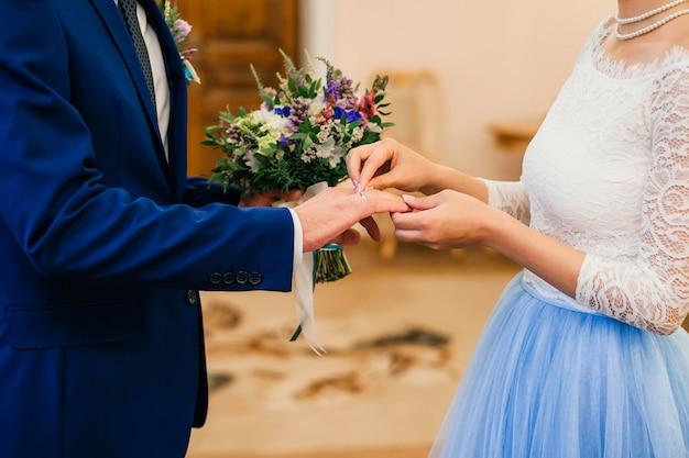 La mariée porte une bague en or au doigt du marié au mariage