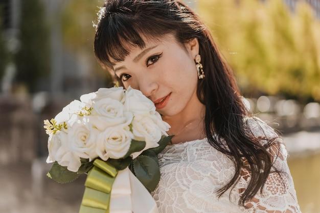 Mariée posant avec beau bouquet de fleurs