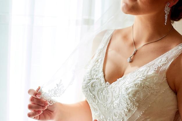Mariée posant à côté de rideaux blancs