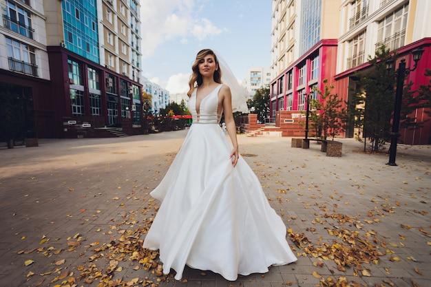 Mariée posant dans une fille verte de parc dans une robe blanche sur fond de vert.