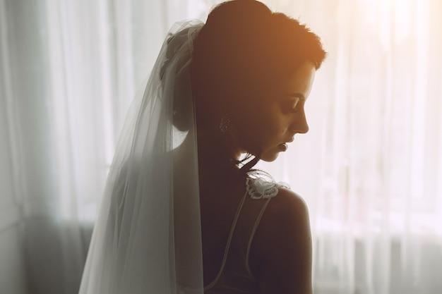 Mariée posant dans une grande fenêtre sur l'appareil photo