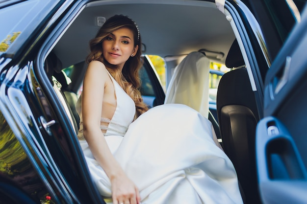Une mariée prend des photos dans la voiture noire.