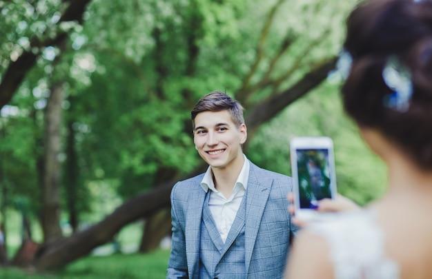 La mariée prend des photos du marié
