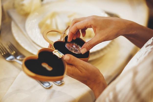 La mariée prend une pièce avec un trou de serrure d'une poitrine en forme de coeur