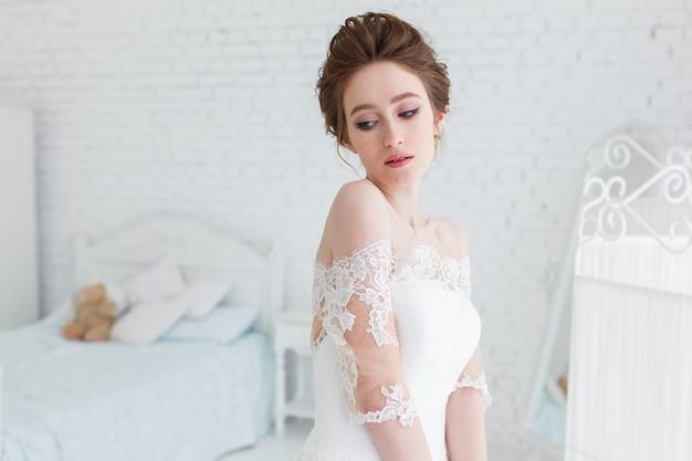 Mariée qui pose en robe de mariée dans le studio sur un fond d'un mur de briques et un lit blanc