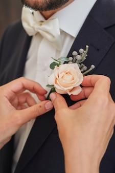 La mariée redresse la rose pâle de la boutonnière du marié