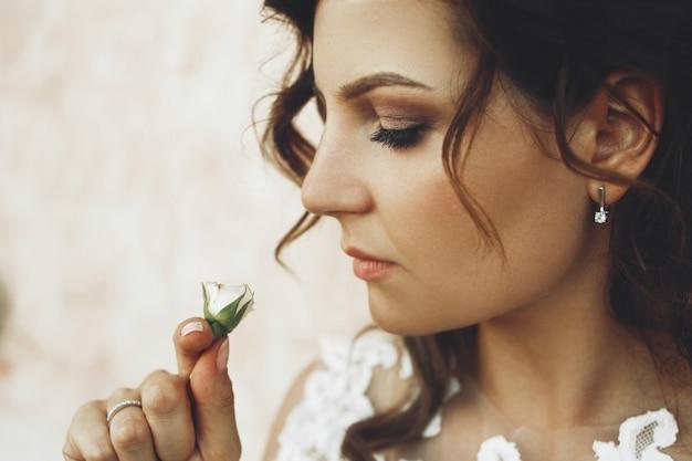 Mariée réfléchie bouclés se tient devant un vieux mur de pierre et sent un peu rose