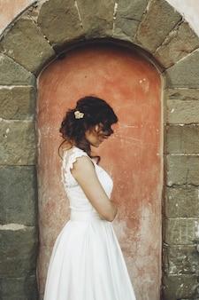 Mariée réfléchie bouclés se tient devant un vieux mur de pierre