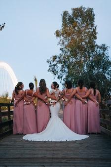 Mariée regardant la caméra et les demoiselles d'honneur par derrière en voyant leurs robes