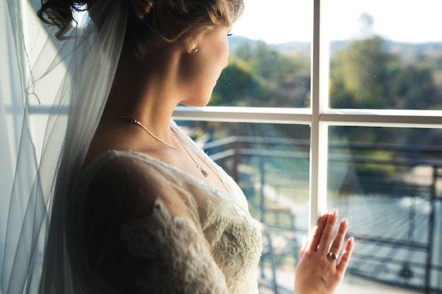 Mariée regardant par la fenêtre de la chambre d'hôtel