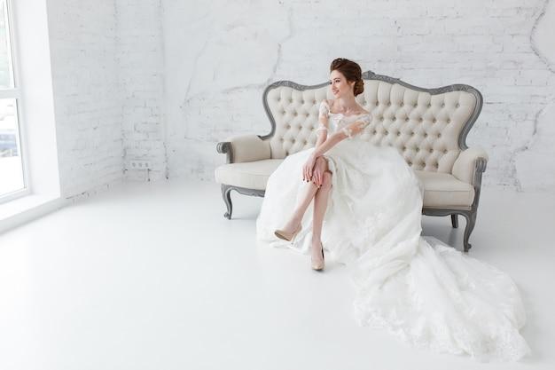 Mariée regardant par la fenêtre, elle attend le marié assis sur un grand canapé classique.