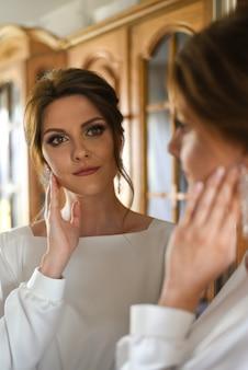 La mariée regarde dans le miroir avant le mariage du matin