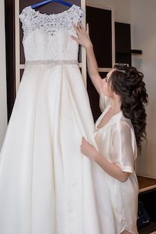 La mariée regarde la robe de mariée suspendue au cintre