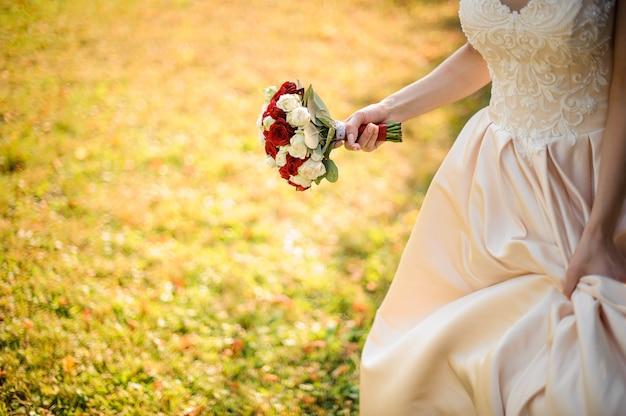 Mariée en robe blanche avec un beau bouquet de roses rouges dans le parc verdoyant. conception du mariage