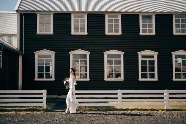 La mariée en robe blanche avec un bouquet dans les mains va sur fond de fenêtres en bois