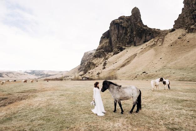 La mariée en robe blanche et un bouquet dans ses mains caressant un cheval avec une crinière noire au visage