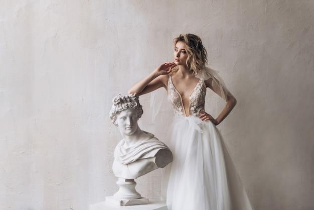 Mariée en robe blanche s'appuyant sur la sculpture. portrait de la belle mariée en robe de mariée blanche avec décolleté. robe de mariée avec décolleté orné de dentelle
