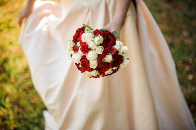 Mariée en robe blanche tenant un beau bouquet de roses rouges dans le parc verdoyant. conception du mariage