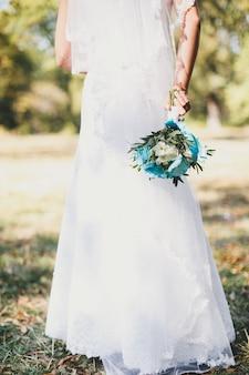 Mariée en robe blanche tenant le bouquet de mariage